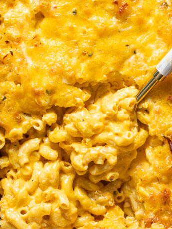 southern baked Mac and cheese in baking dish with gold serving spoon