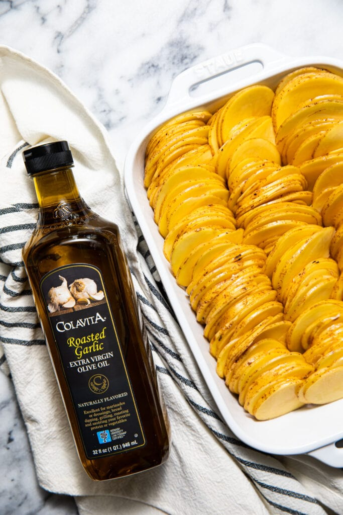 thinly sliced potatoes in white baking dish with colavita olive oil on the side
