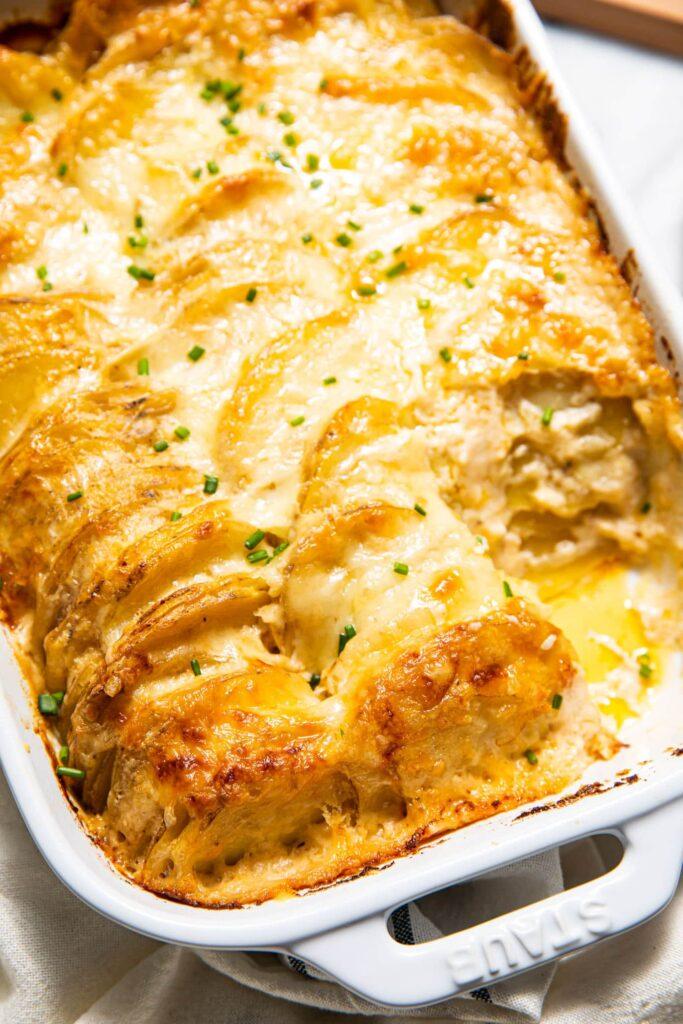scalloped potatoes in white baking dish