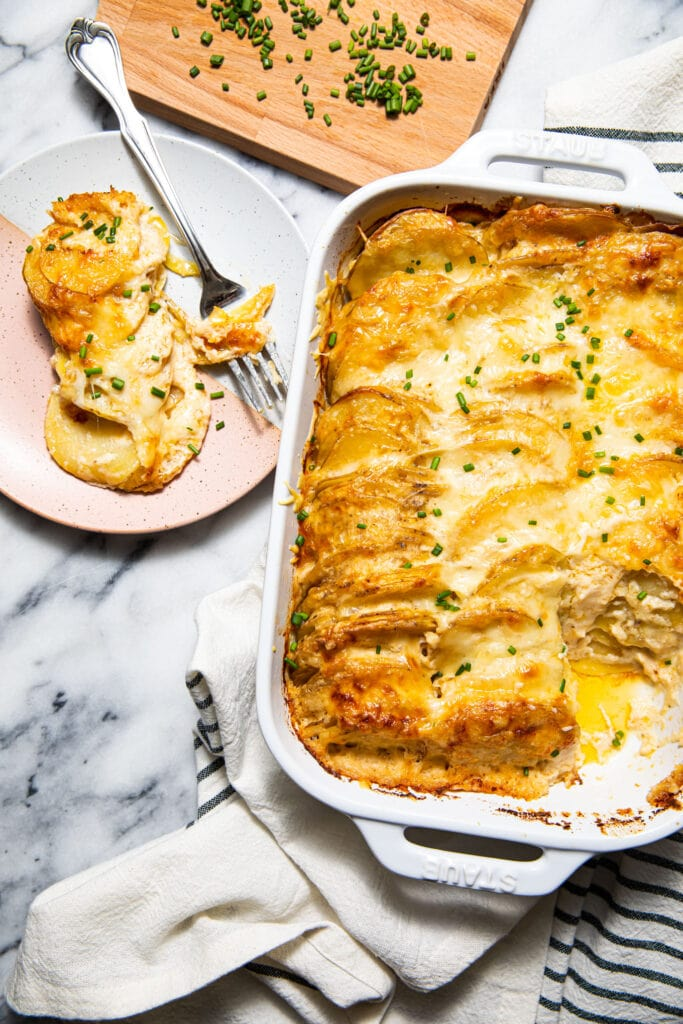 scalloped potatoes in white baking dish with small pink and white plate on marble surface