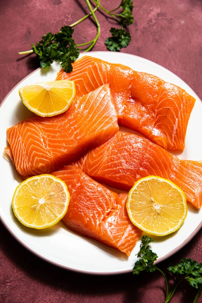 raw salmon filets with lemon slices on white plate