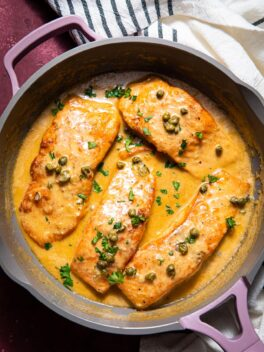creamy salmon piccata in purple skillet with striped linen on the side