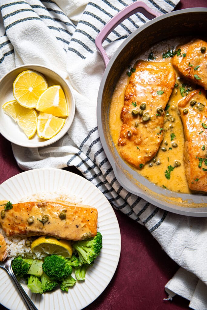 creamy salmon piccata in purple skillet with white plate on the side
