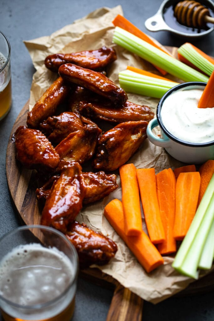 honey chipotle chicken wings on wood board with carrots and celery