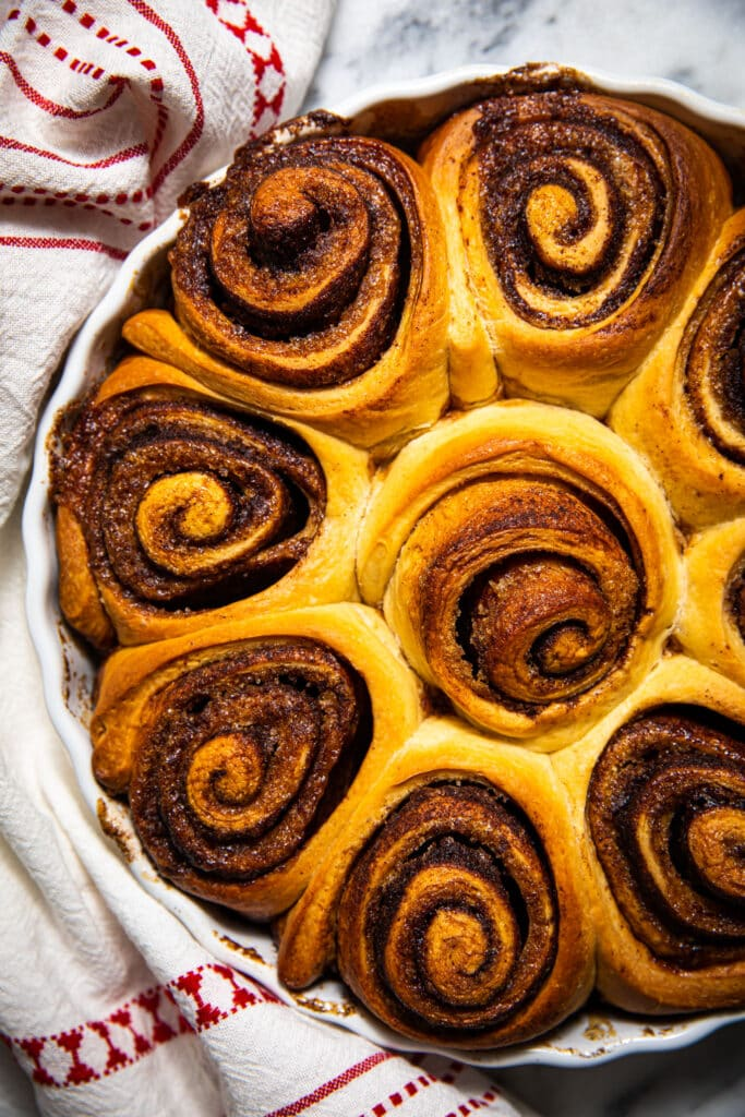 non-iced brown butter eggnog cinnamon rolls in round baking dish