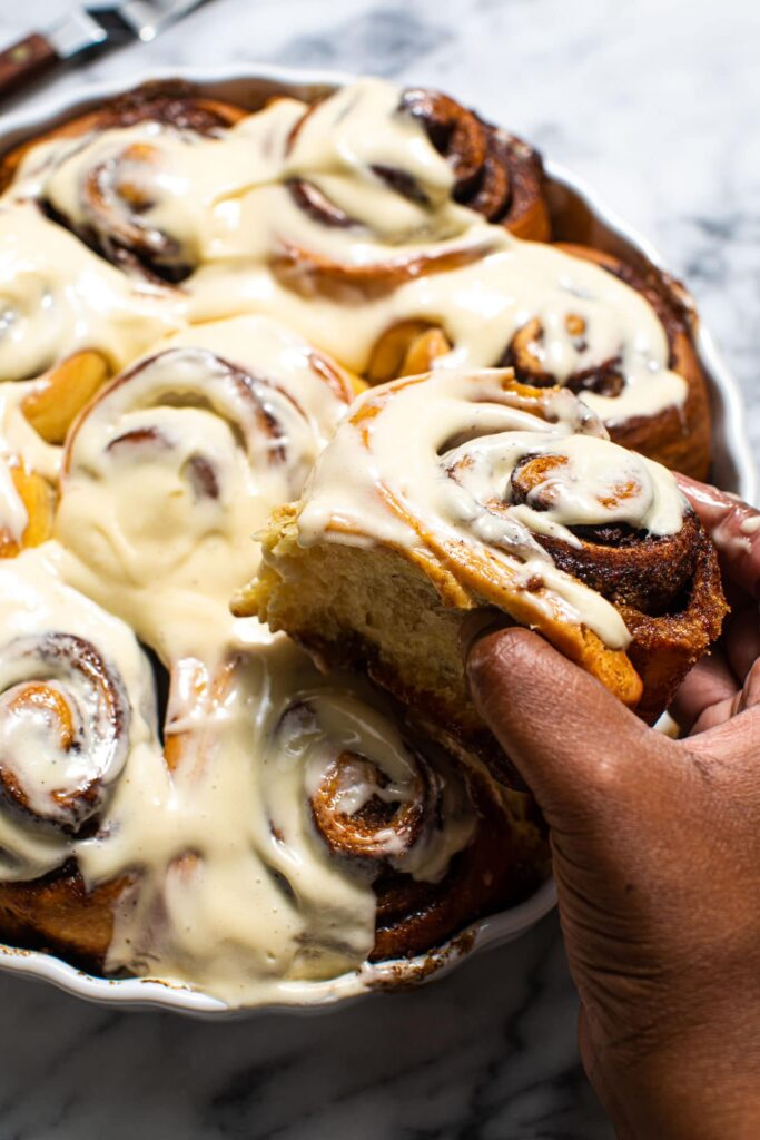 black hand holding brown butter eggnog cinnamon roll over round baking dish