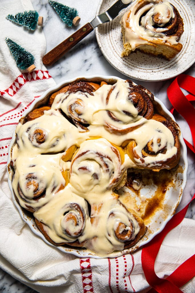 brown butter cinnamon roll in round baking dish with striped linen