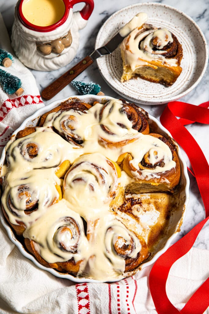 brown butter eggnog cinnamon rolls in round baking dish with red striped linen on marble surface