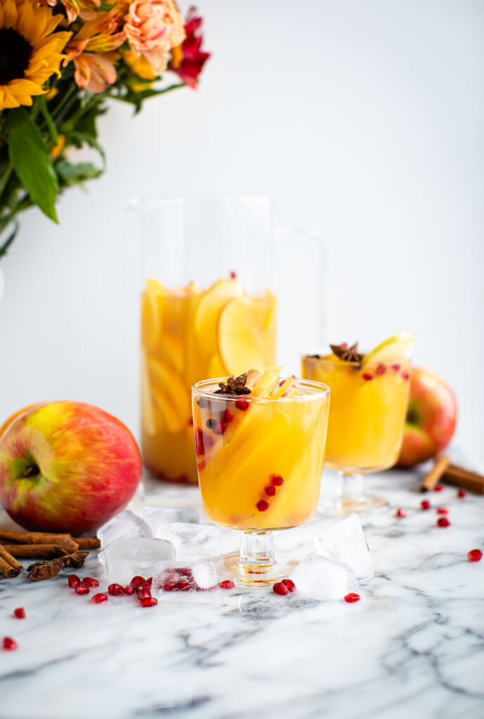 apple sangria in glasses on marble surface with flowers in the background