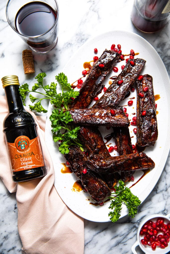 pomegranate balsamic glazed ribs on oval white platter with colavita balsamic glaze on the side