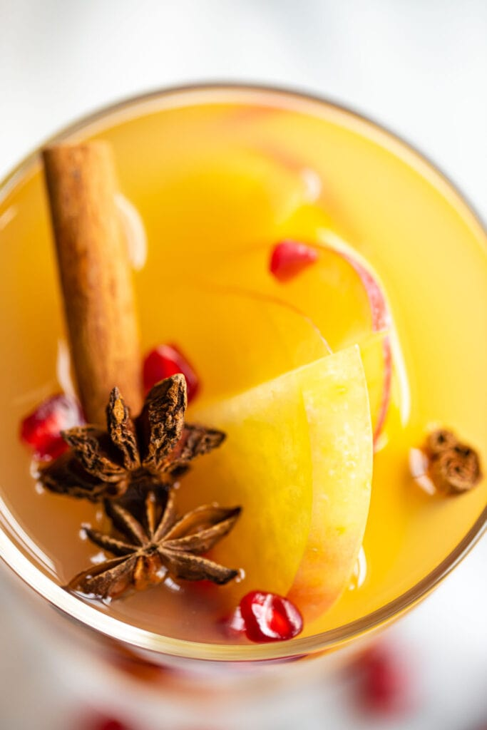 close up of apple sangria in glass with star anise and apple slices on top