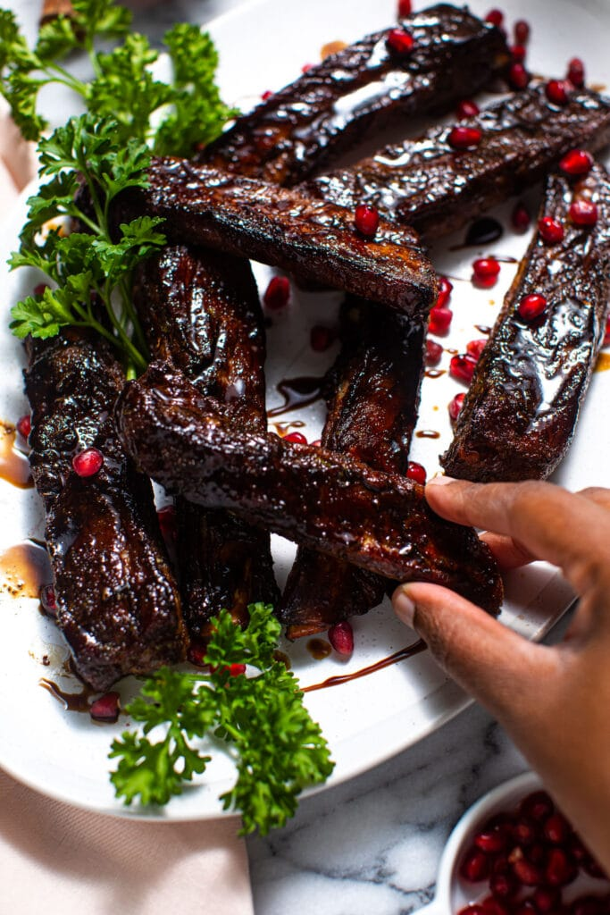 black hand grabbing balsamic ribs off of white plate