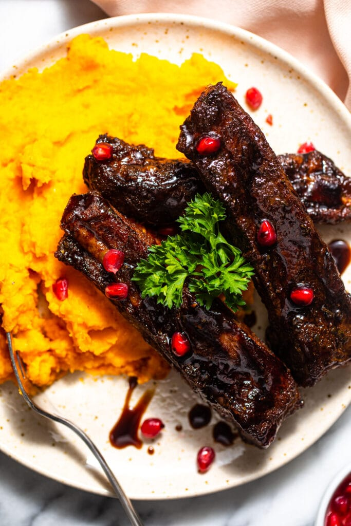 pomegranate balsamic glazed ribs on top of mashed sweet potatoes on speckled plate