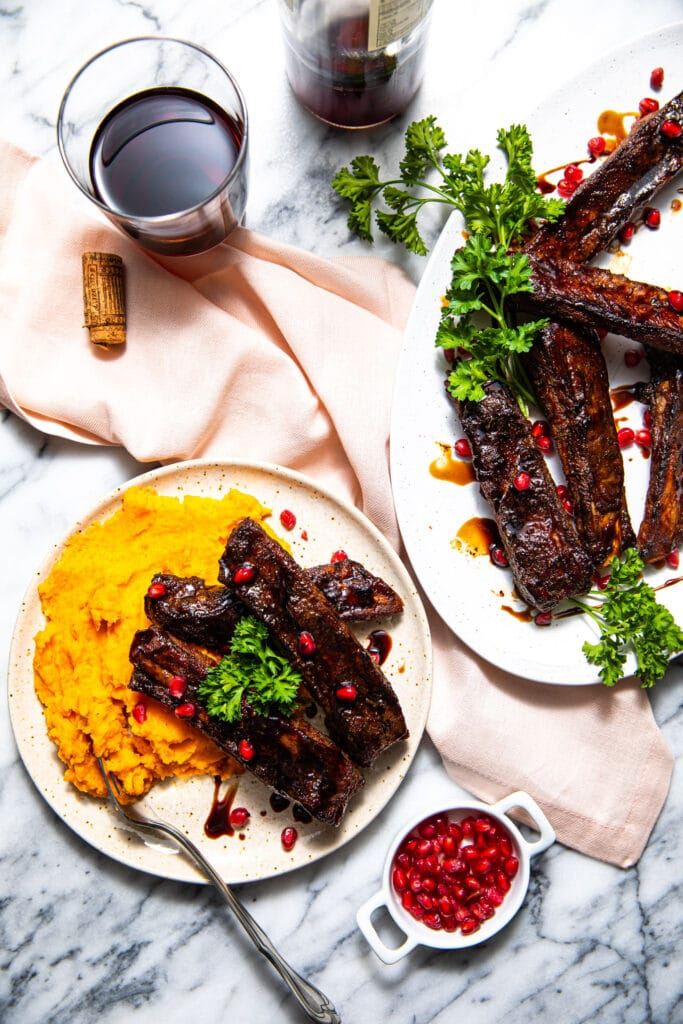 pomegranate balsamic glazed ribs on platter and plate with mashed sweet potatoes