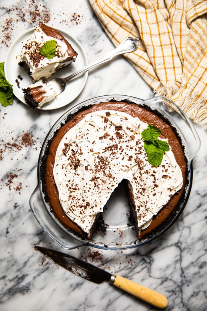 mocha chocolate cream pie with small plate on marble surface