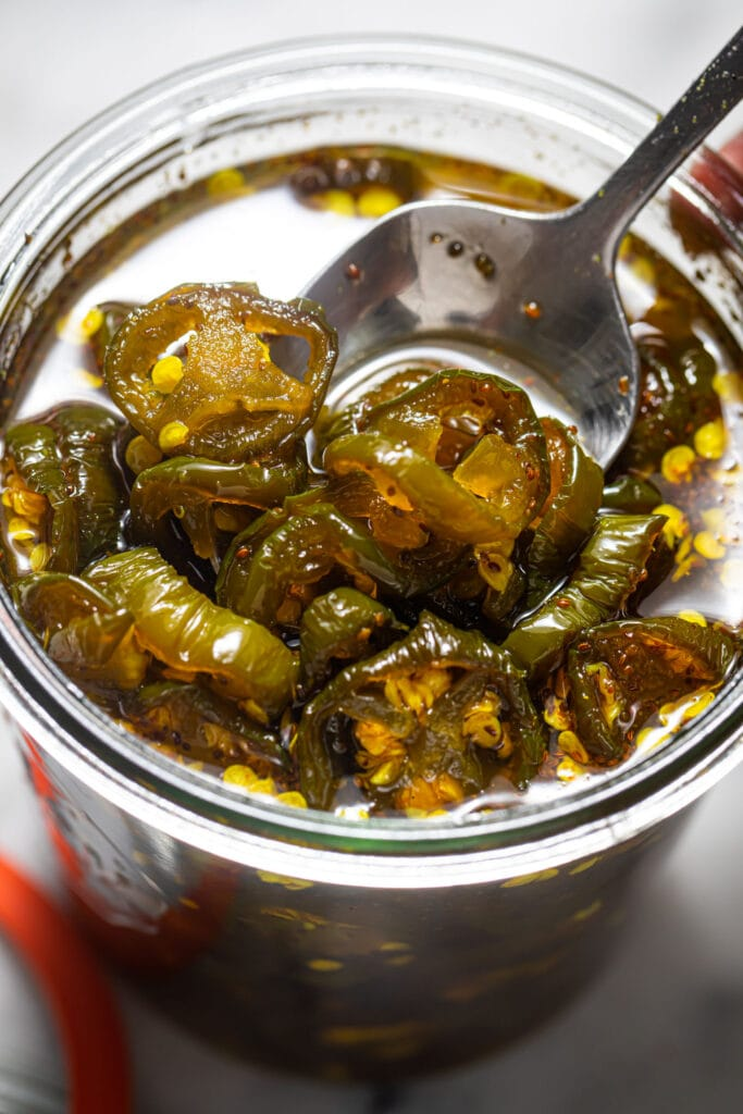 spoon going into a jar of candied jalapeños