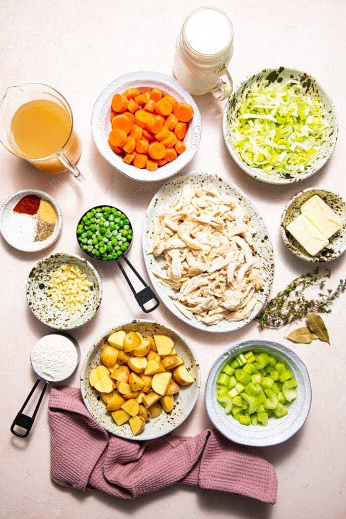 ingredients for chicken pot pie on pink surface