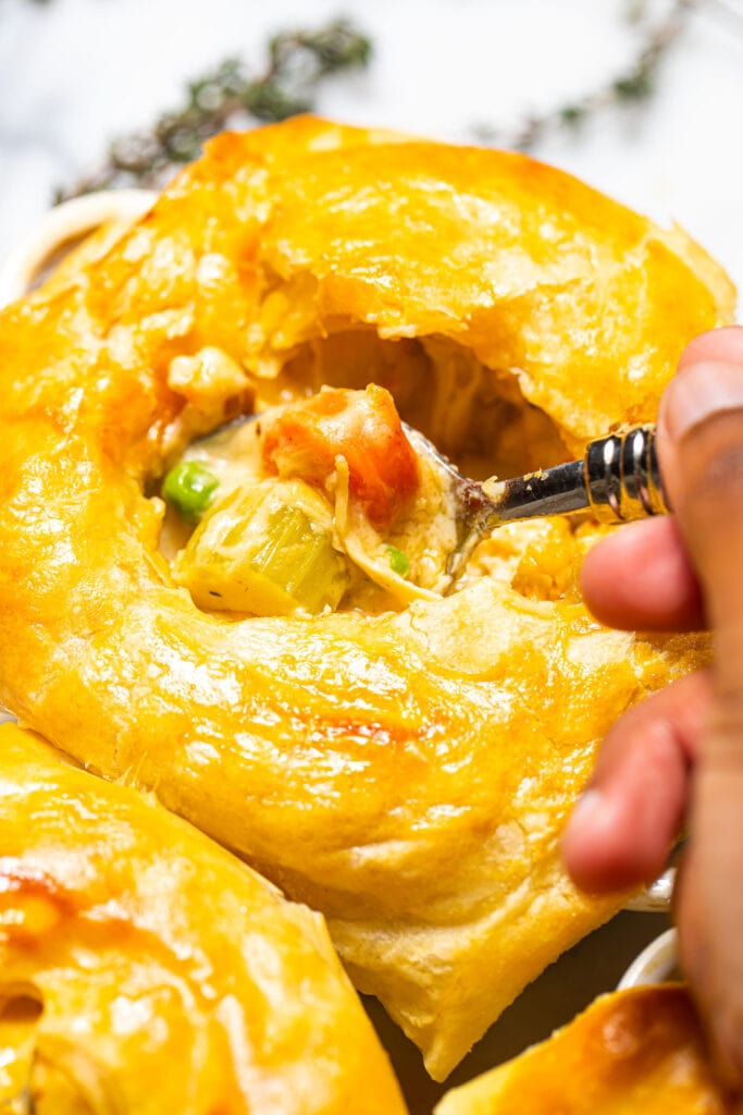 black hand taking a spoonful of puff pastry chicken pot pie