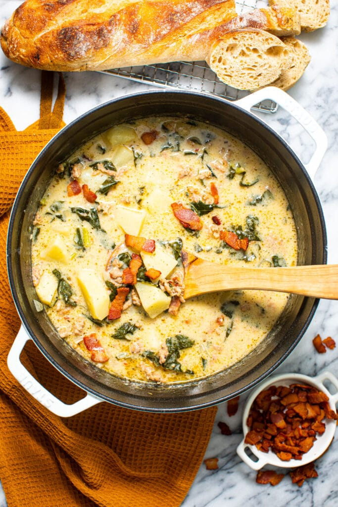large white pot full of Zuppa Toscana on marble surface