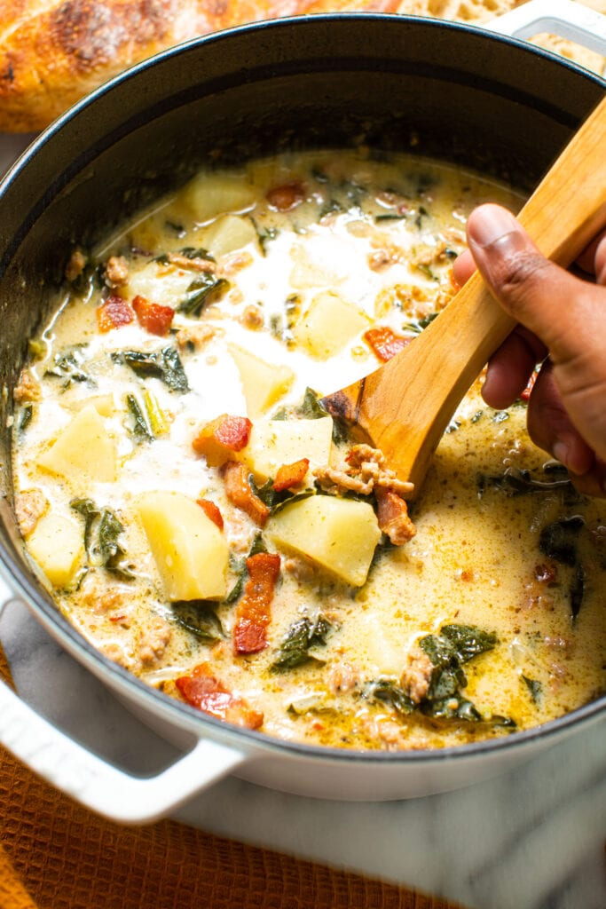 black hand with ladle in pot of Zuppa Toscana