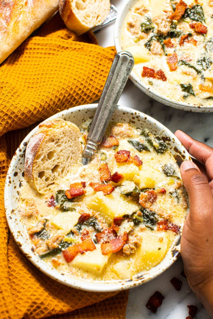 black hand holding the side of speckled bowl full of Zuppa Toscana