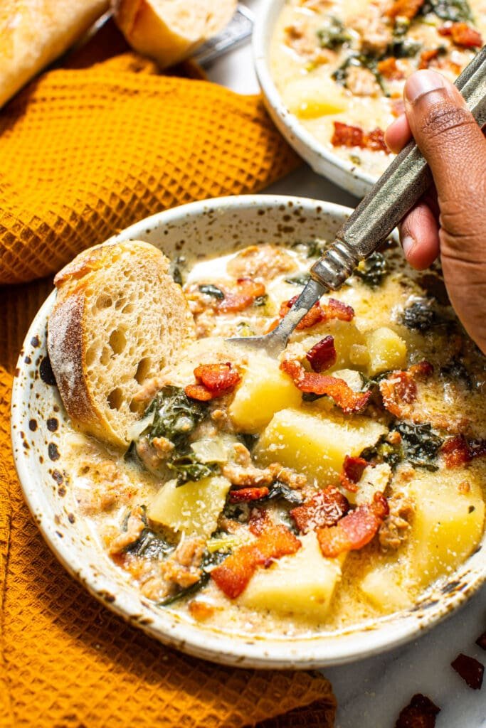 black hand holding spoon in speckled bowl of Zuppa Toscana