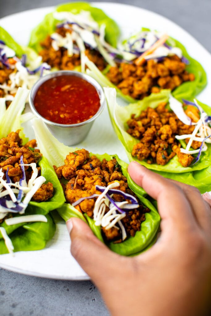 black hand grabbing curry chicken lettuce wrap on white plate