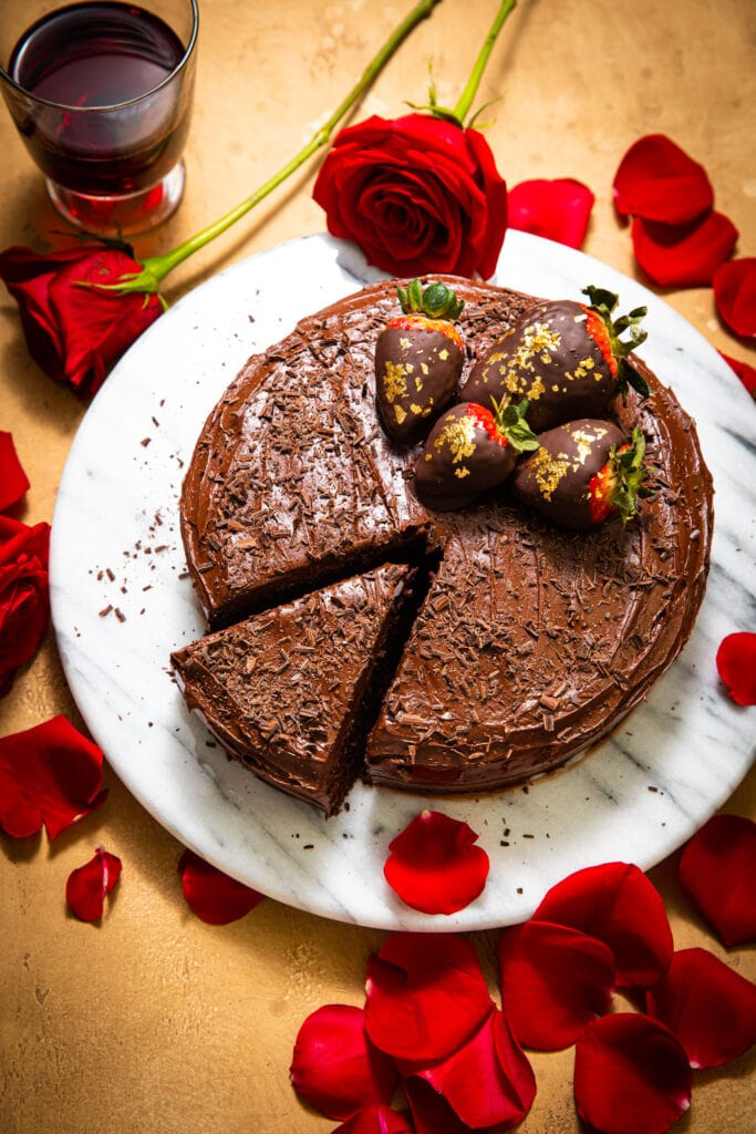 chocolate cake with strawberries on marble cake platter