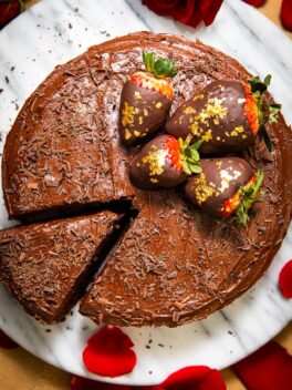 frosted chocolate cake with strawberries on marble cake platter