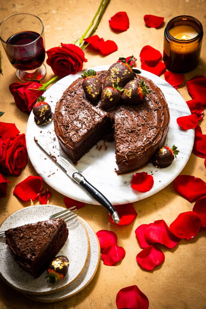 sliced chocolate cake with red roses on beige surface