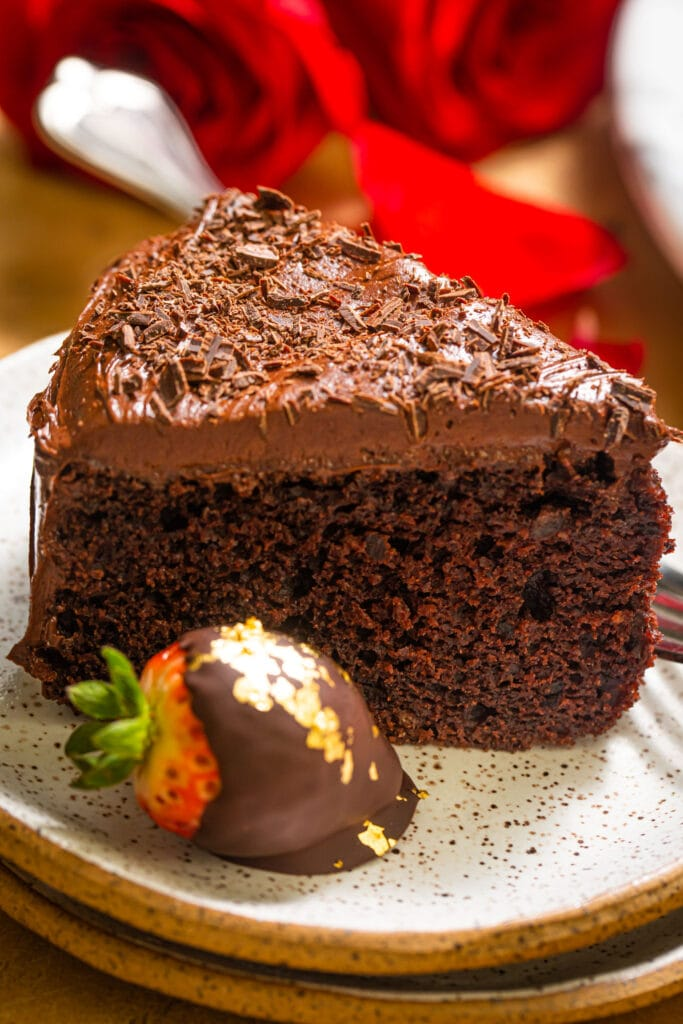 slice of chocolate cake with strawberry on small speckled plate