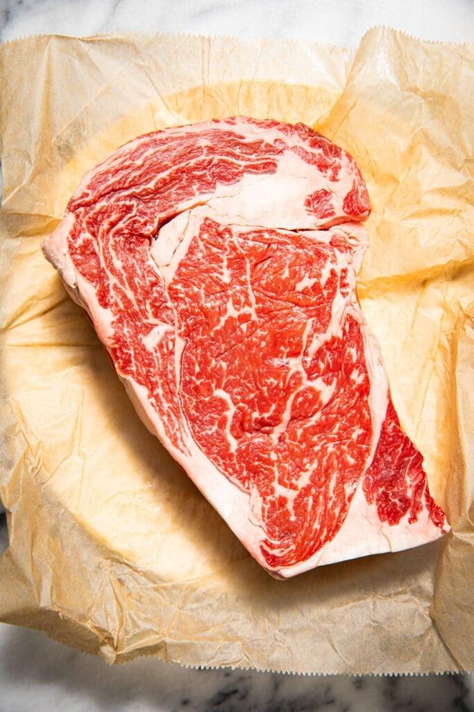 raw ribeye steak on piece of parchment paper
