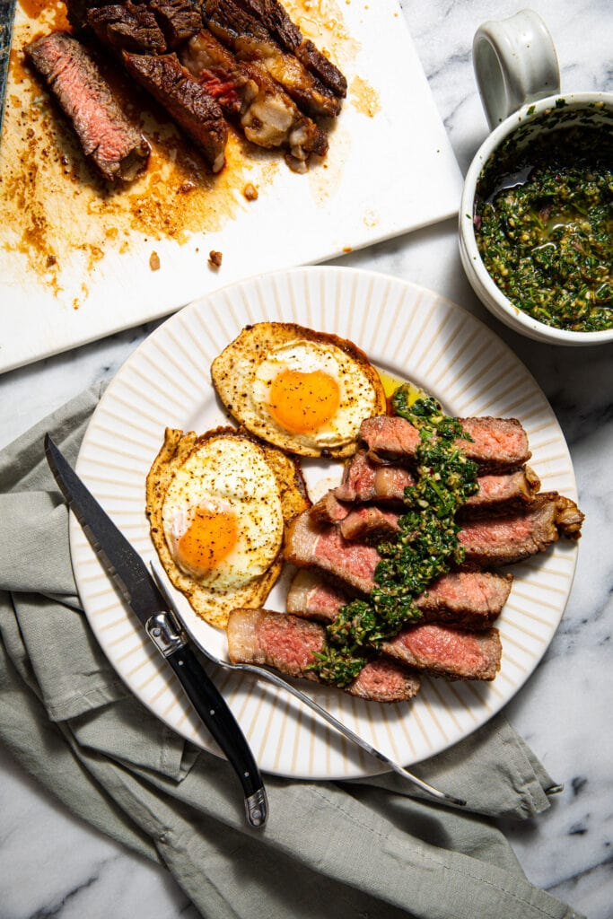 steak and eggs with fork and knife on white plate with gray linen