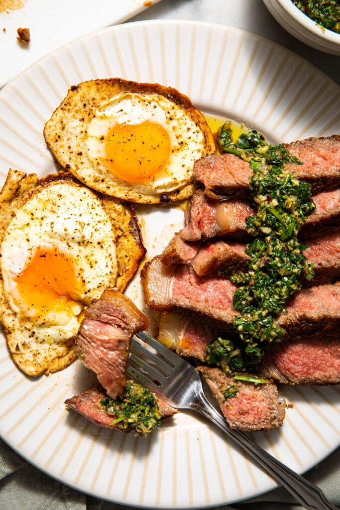 steak and eggs on white plate with fork
