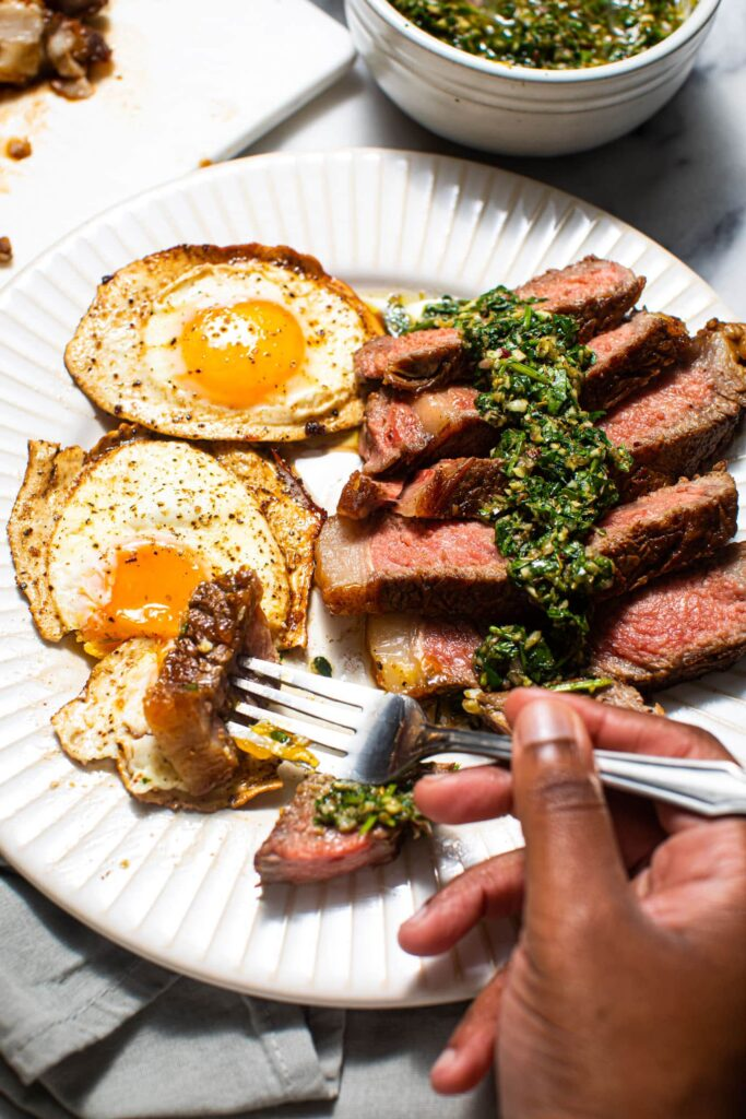 black hand with forkful of steak and eggs on white plate