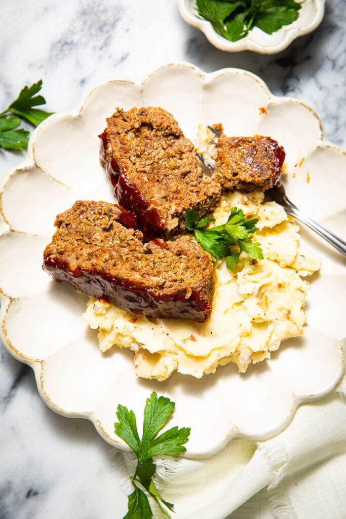sliced meatloaf on top of mashed potatoes on white scalloped plate