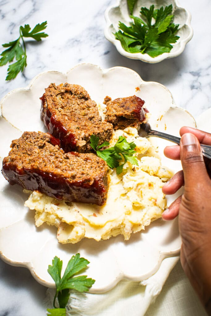 black hand taking a forkful of meatloaf on white scalloped plate
