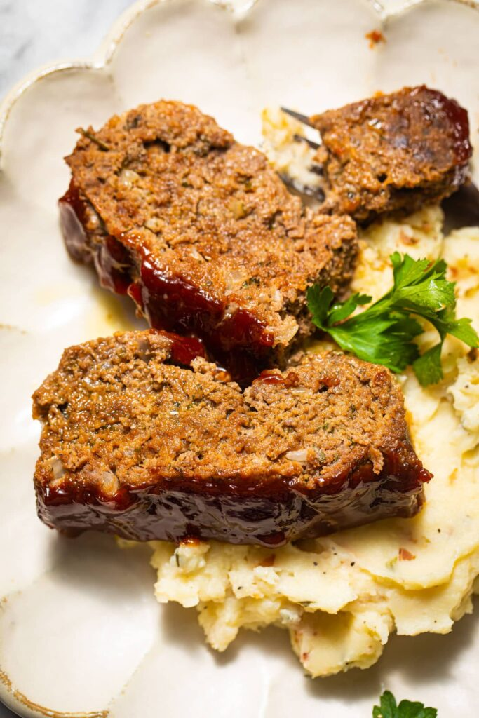 meatloaf slices on top of mashed potatoes on white plate