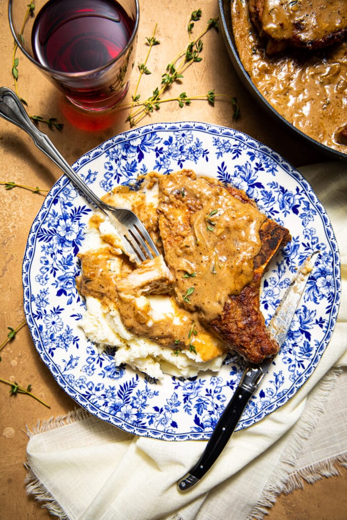 smothered pork chops on top of mashed potatoes on blue and white plate with fork