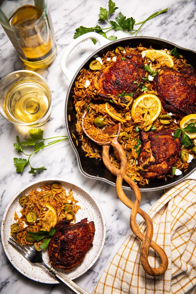 harissa chicken thighs in skillet and on plate on marble surface