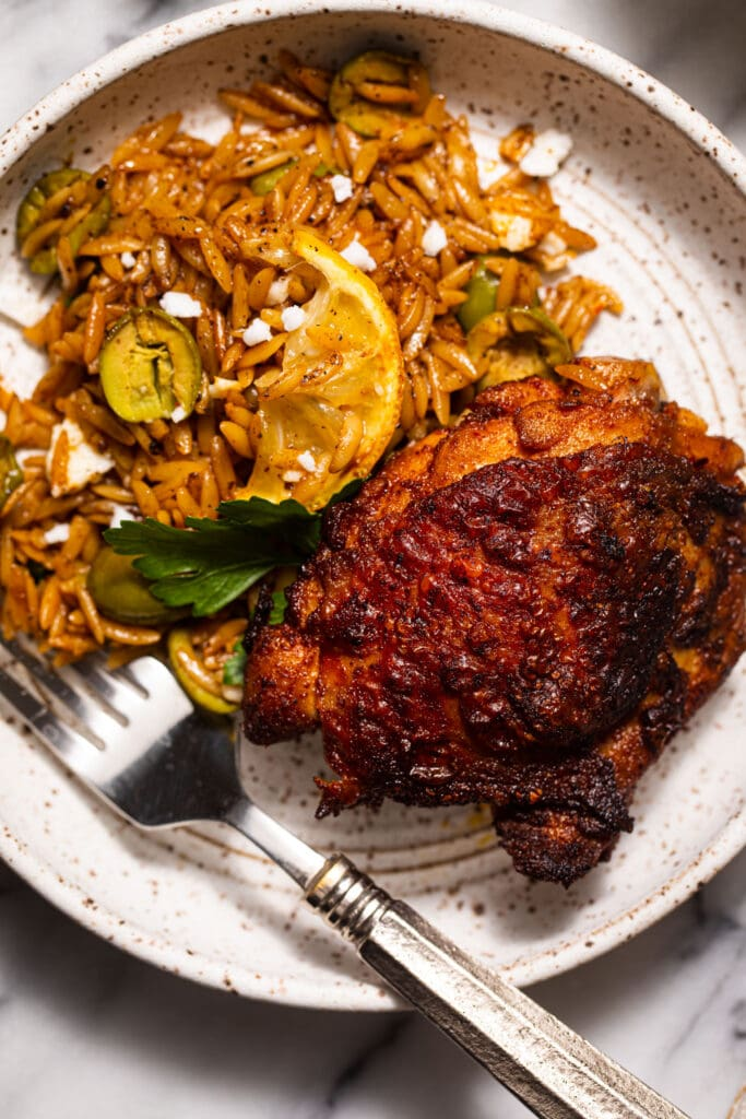 harissa chicken with olives and orzo on small speckled plate with silver fork