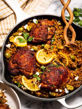 harissa spiced chicken thighs in white skillet with olives and orzo