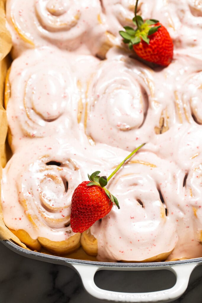 iced strawberry sweet rolls with fresh strawberries in baking dish
