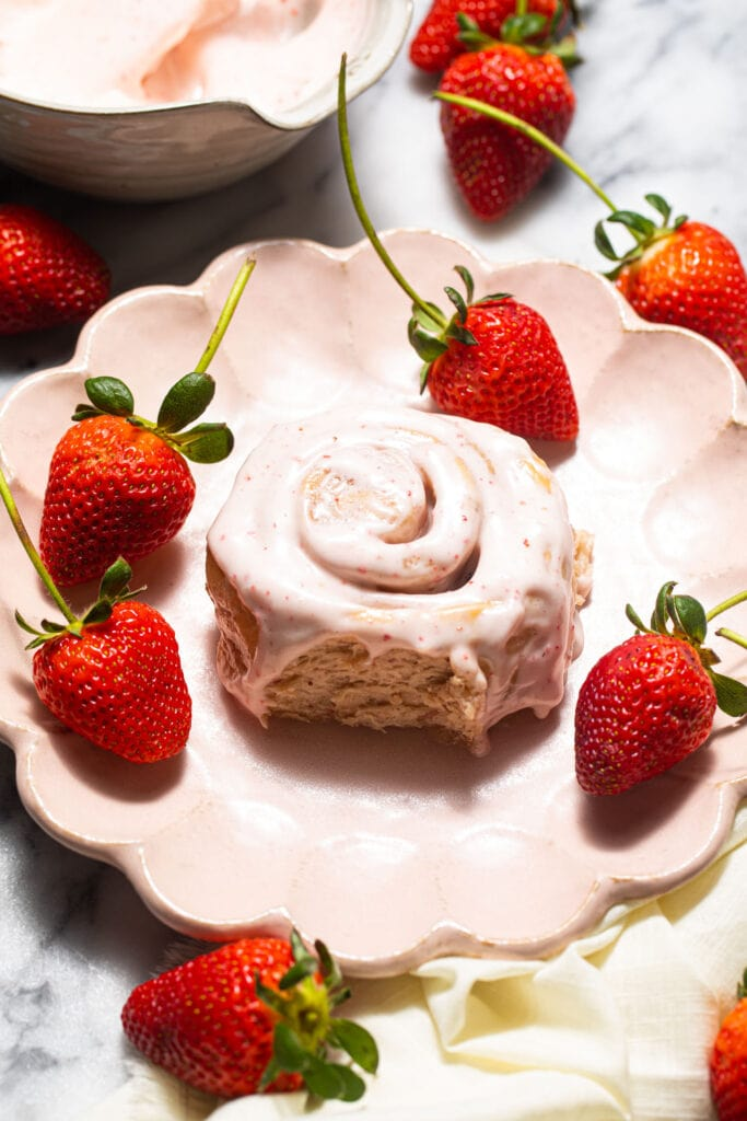 strawberry sweet roll on pink scalloped plate with fresh strawberries around it