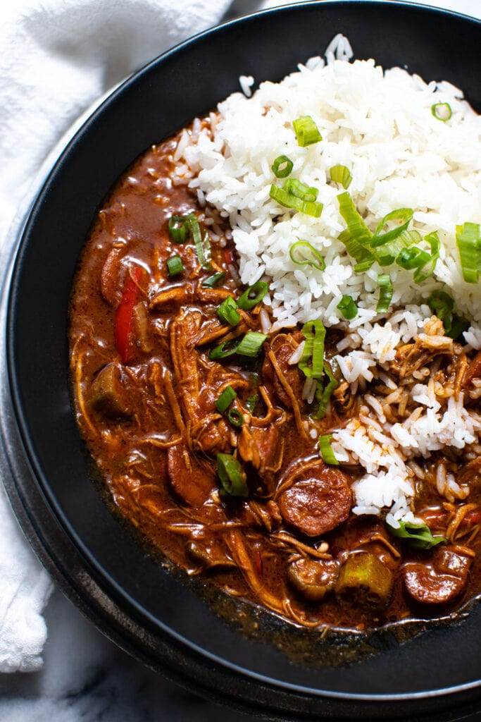 chicken and sausage gumbo with white rice in black bowl
