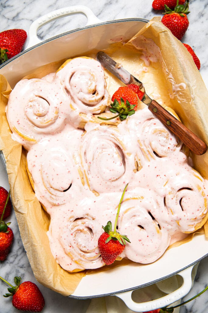 strawberry sweet rolls in white baking dish with strawberries