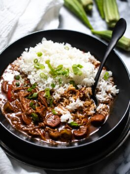 chicken and sausage gumbo with white rice in black bowl with black spoon