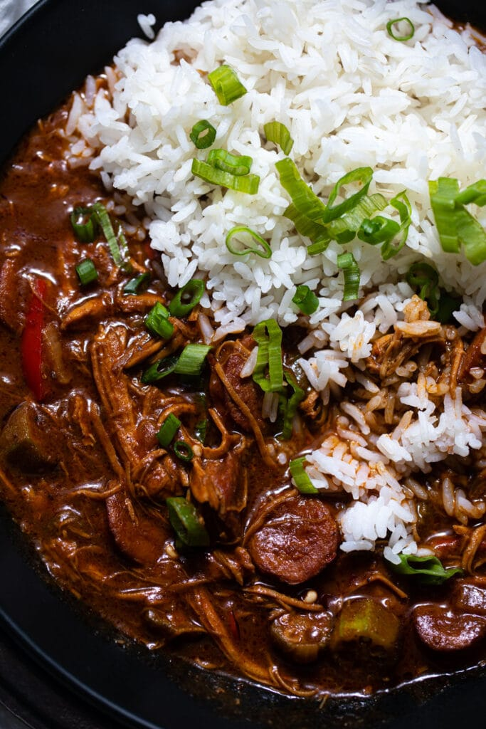 close up of chicken and sausage gumbo with white rice in black bowl