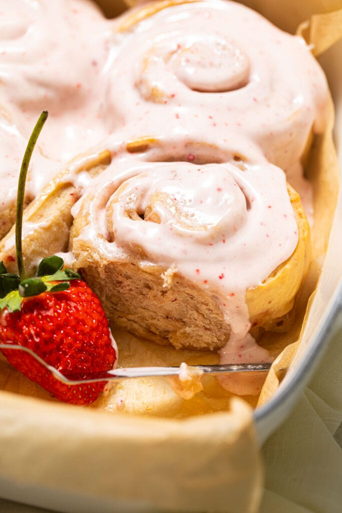 strawberry sweet rolls in baking dish with strawberry