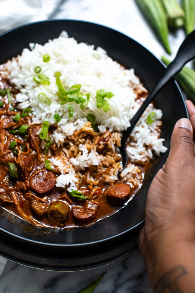 black hand holding the side of black bowl filled with chicken and sausage gumbo and white rice